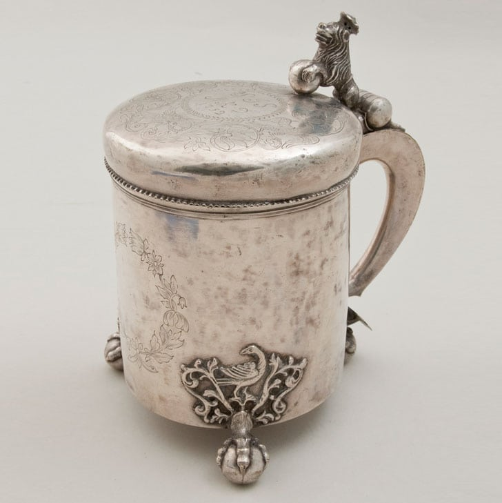 Tankard with three claw-and-ball feet above which are cast acanthus motifs with a bird in the center - Norwegian Metalworking