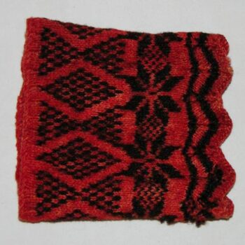 Wrist warmers hand-knit using what appears to be vegetable dyed red and black sheep wool