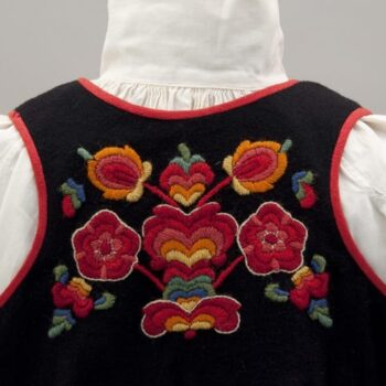 This dress has a black wool skirt with red trim around the neckline and armholes - Textiles