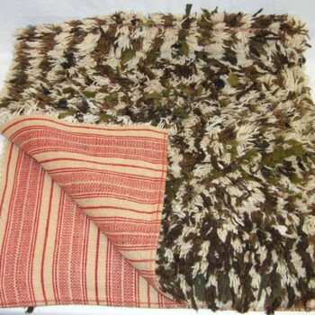One side of this coverlet, or båtrye, resembles a rug or carpet with wool yarn and pieces of fabric