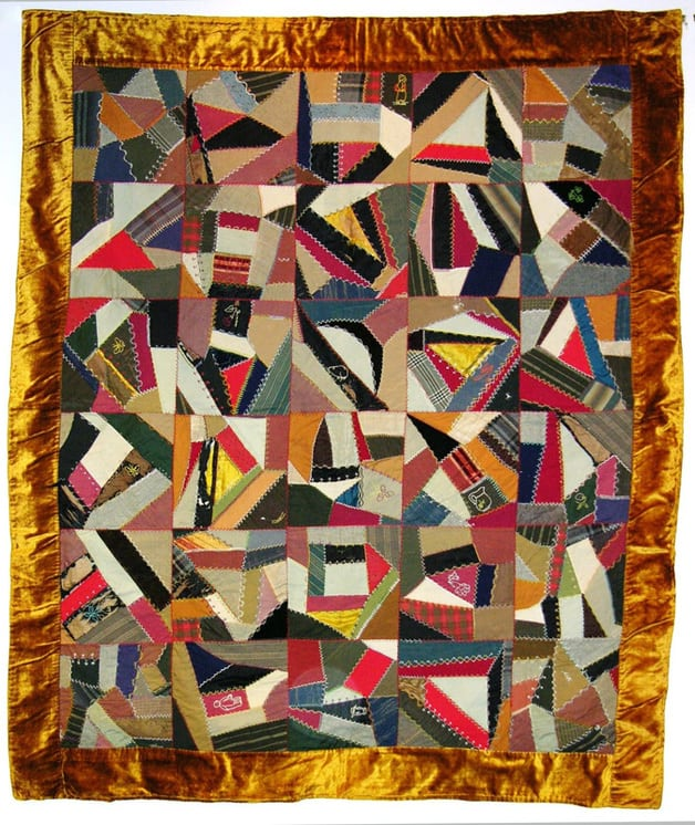 Quilt with seams between the pieces are decorated with a large variety of multicolored stitches