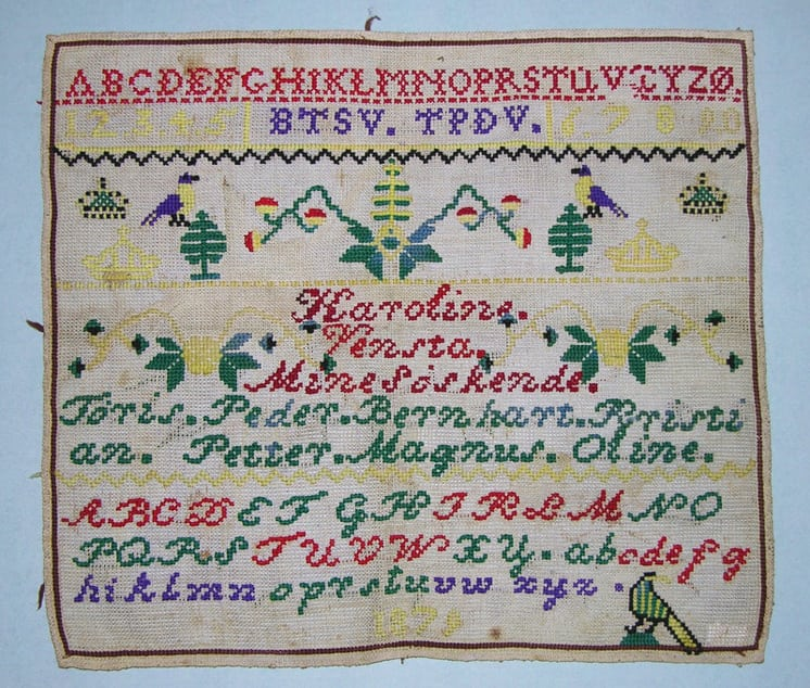 Alphabet sampler (navneduk) was done in bright colored cross-stitches on a fairly coarse canvas backing - Textiles