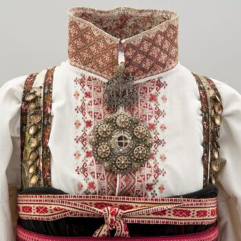 This bunad has a floor-length heavily gathered skirt that joins to a brocaded silk bodice above the bust - Textiles