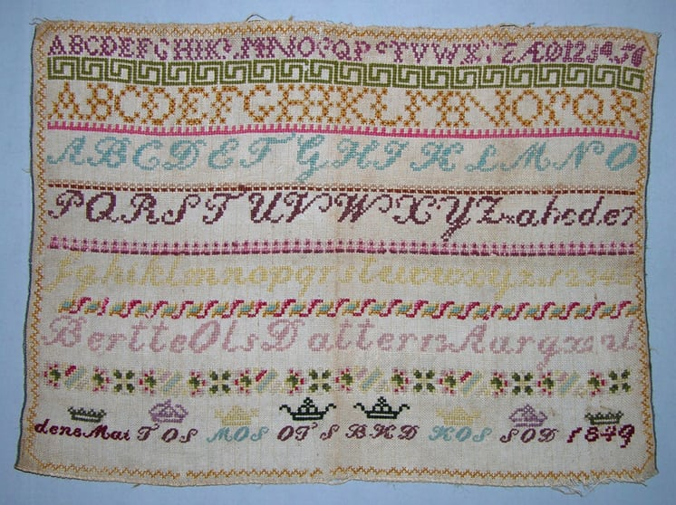 alphabet sampler done on a natural colored canvas-backing in cross-stitch using two strands of wool yarn - Textiles