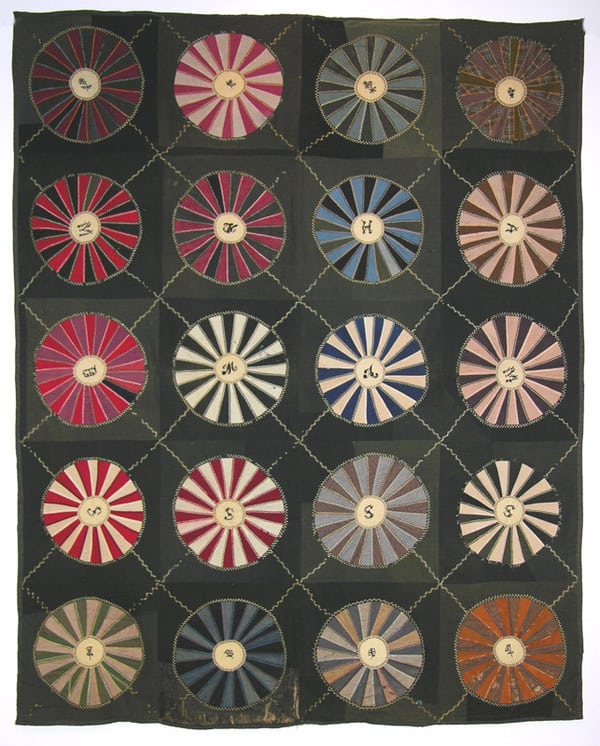 This pieced quilt was made predominantly from wool fabrics in a pattern known as Wagon Wheel or Wheel of Chance - Textiles