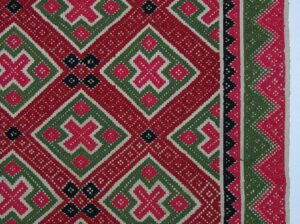 Coverlet with pattern in two-ply wool of diamonds and related geometric forms in two shades of red, green, and dark blue - Textiles