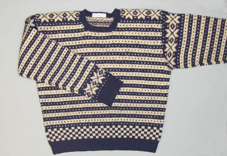 Hand-knit, Fana-style, sweater has dark blue and white lateral bands with contrasting
