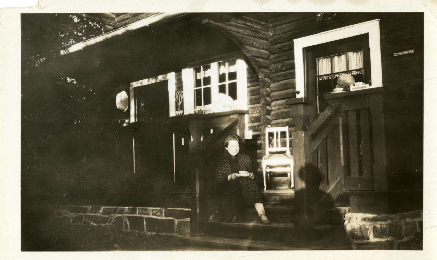 A woman sits on the steps of a front porch. A man sits on the right side of the porch, only his head is visible. The photographers shadow is visible.