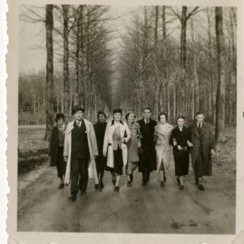 Group of men and women walking down a tree-lined road.