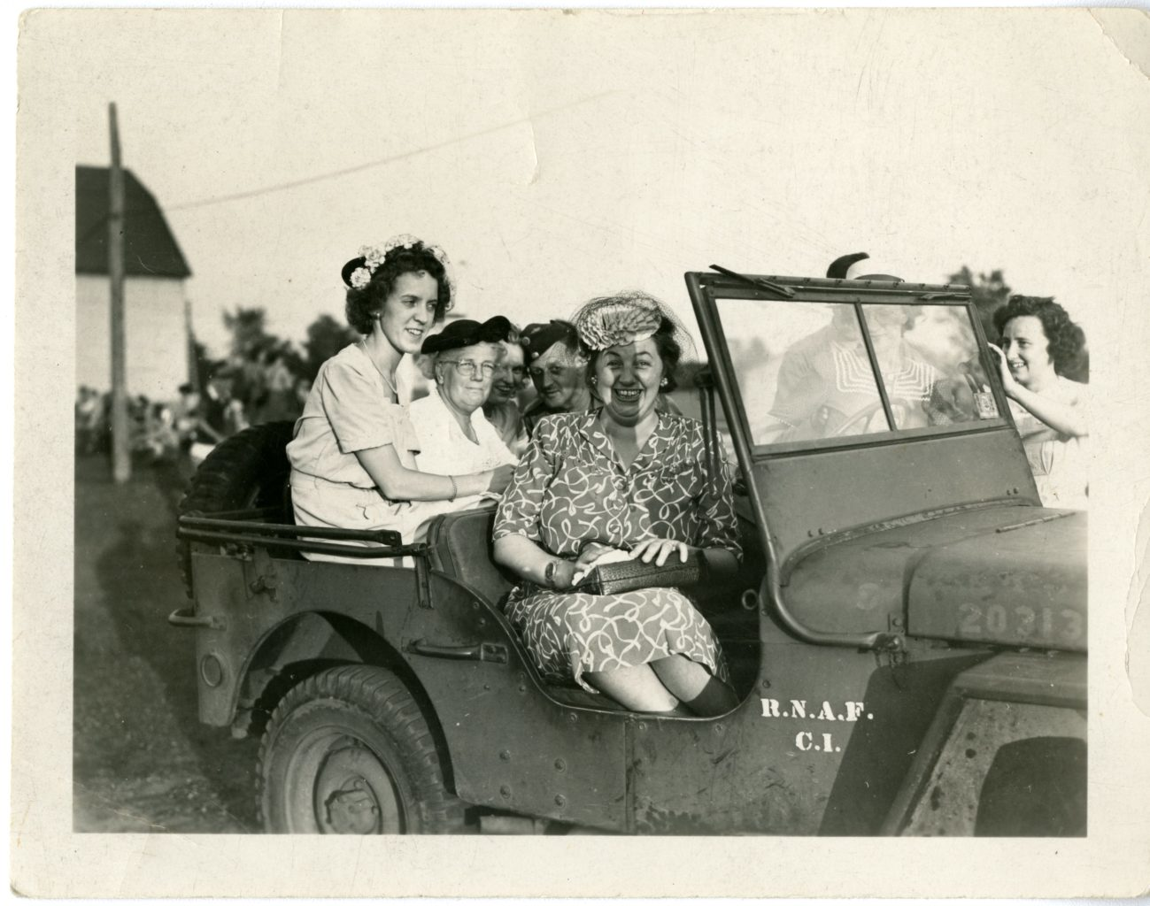 Four women and a man in a jeep.