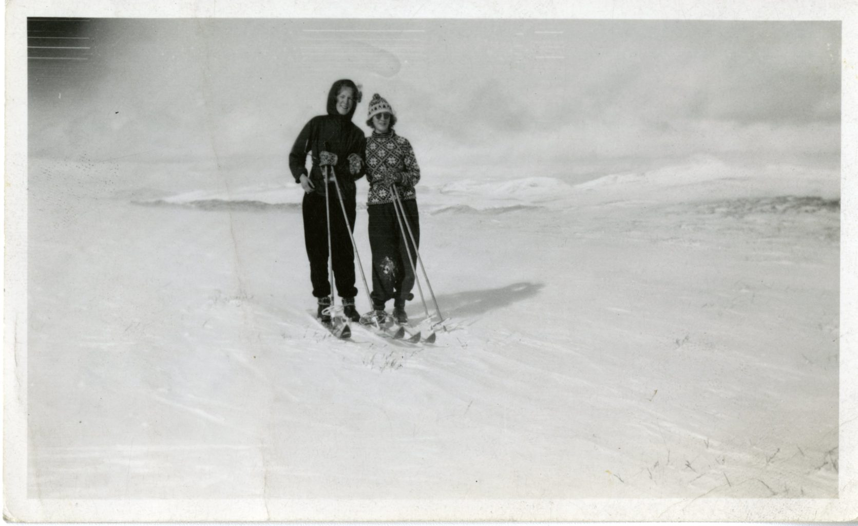 Two women pose while skiing.