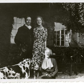 A man, two women, and a dog pose for a photograph.