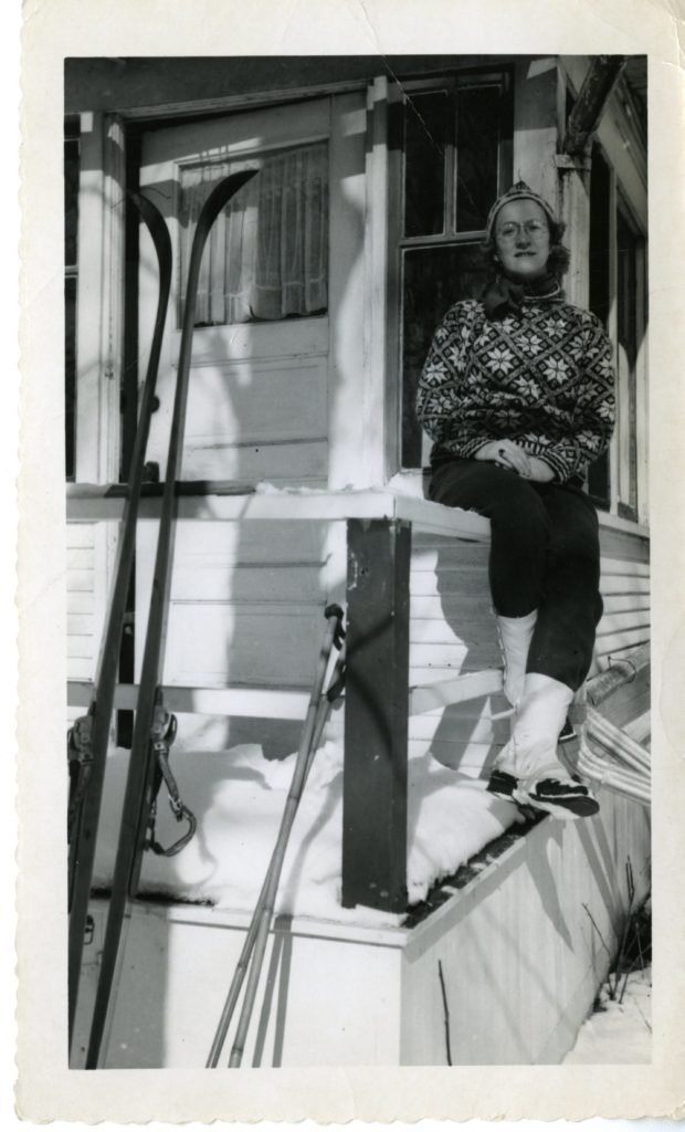 A woman sits on the porch in her ski gear. Possibly Nora Bernts