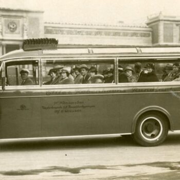 A man poses outside of a long bus with many people inside.