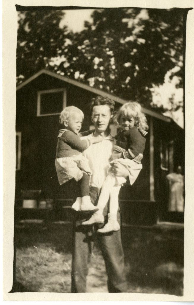 Young man holds two small children with house in background.