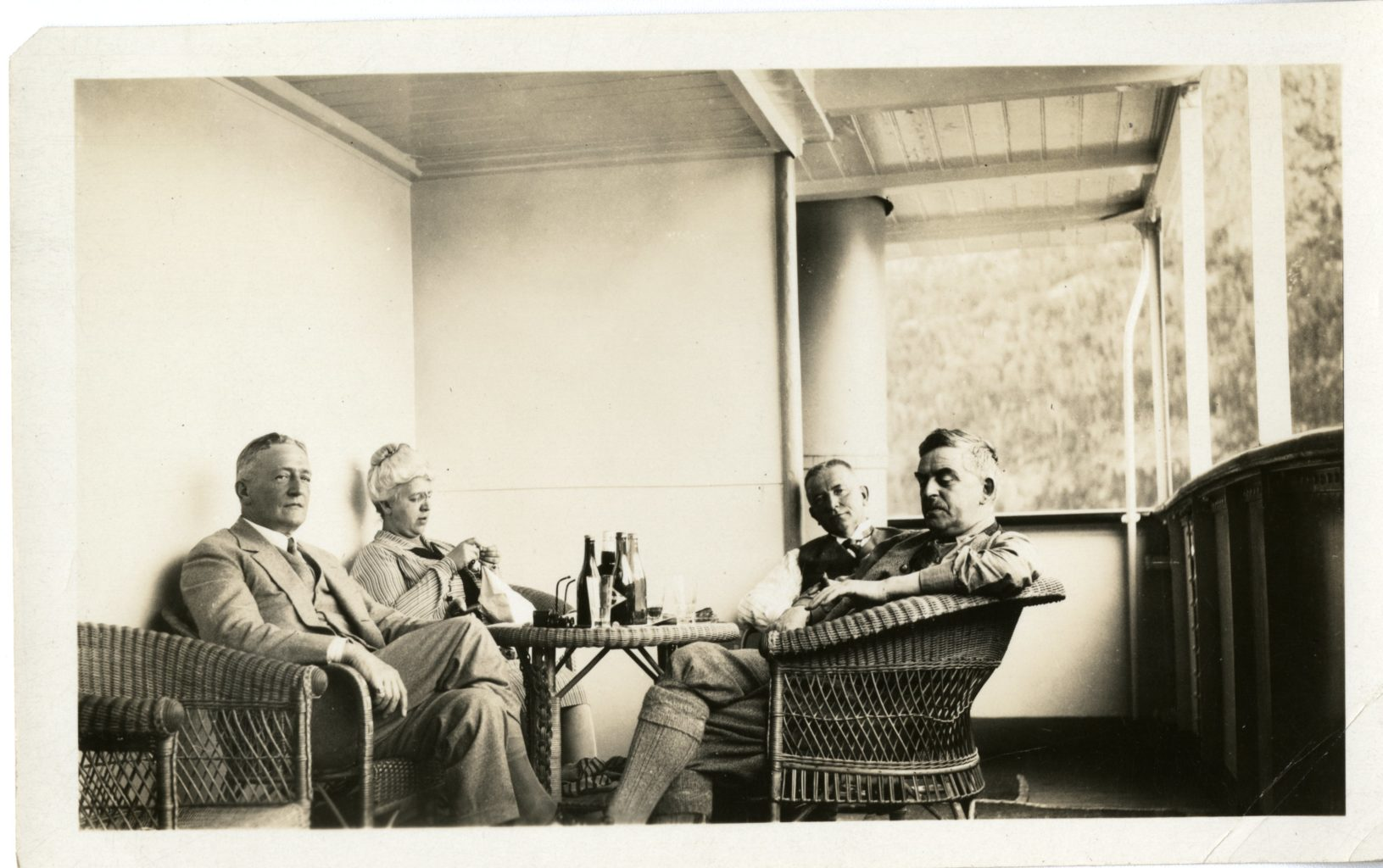 Four individuals sit at table on a porch.