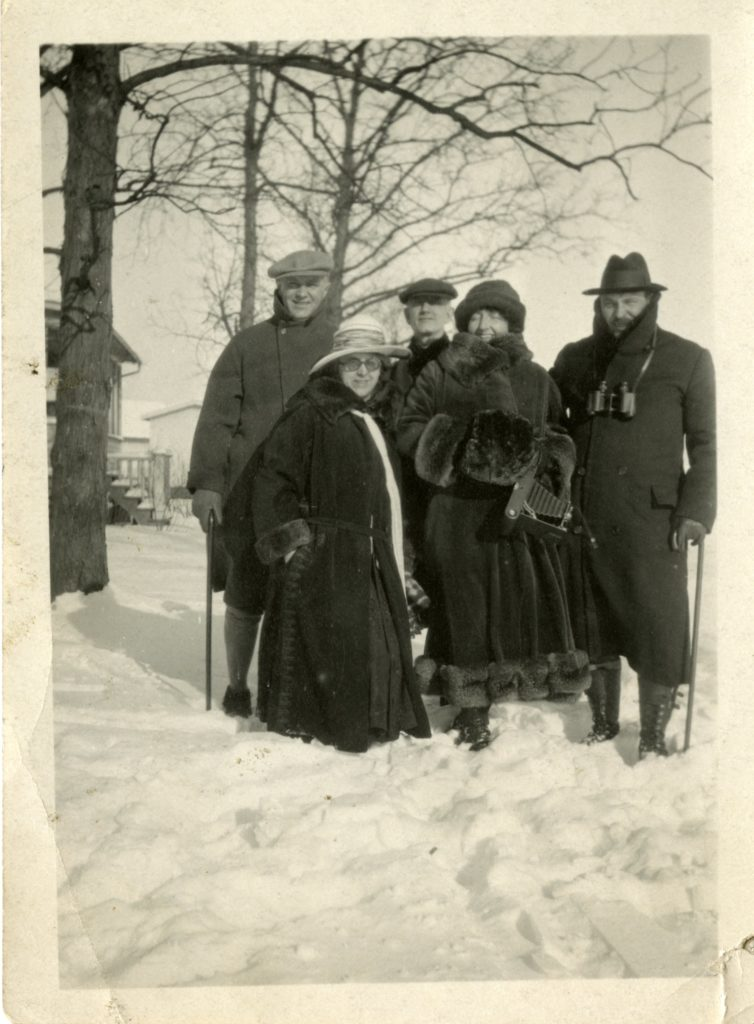 Five people pose outside in the snow for a photograph.