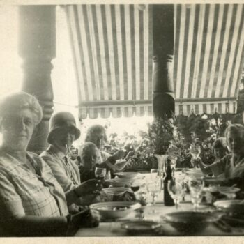 Family sits outside for a meal, all raising a glass.