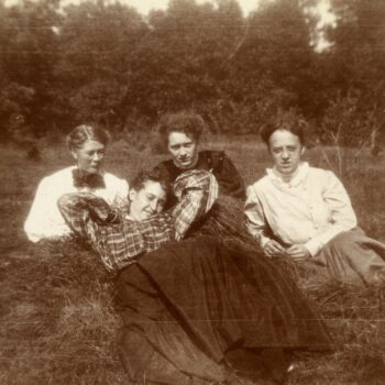 Four women pose for a photograph in a field.