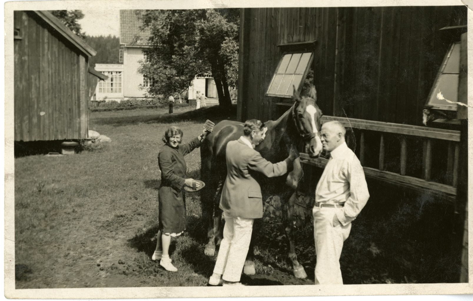Man and woman groom horse on homestead. One man stand to the right.