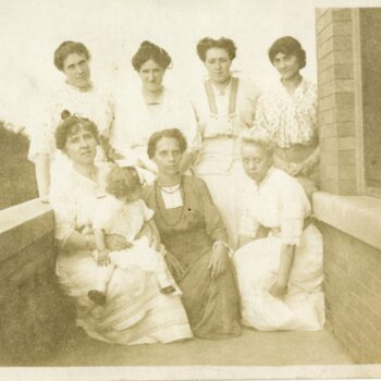 Seven women and young girl pose for photograph outside of building.