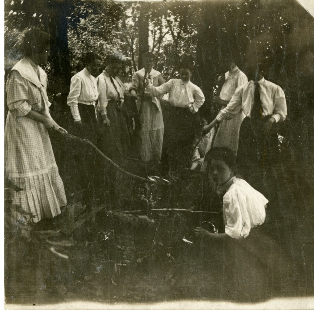 Group of about eight women cook over a fire.