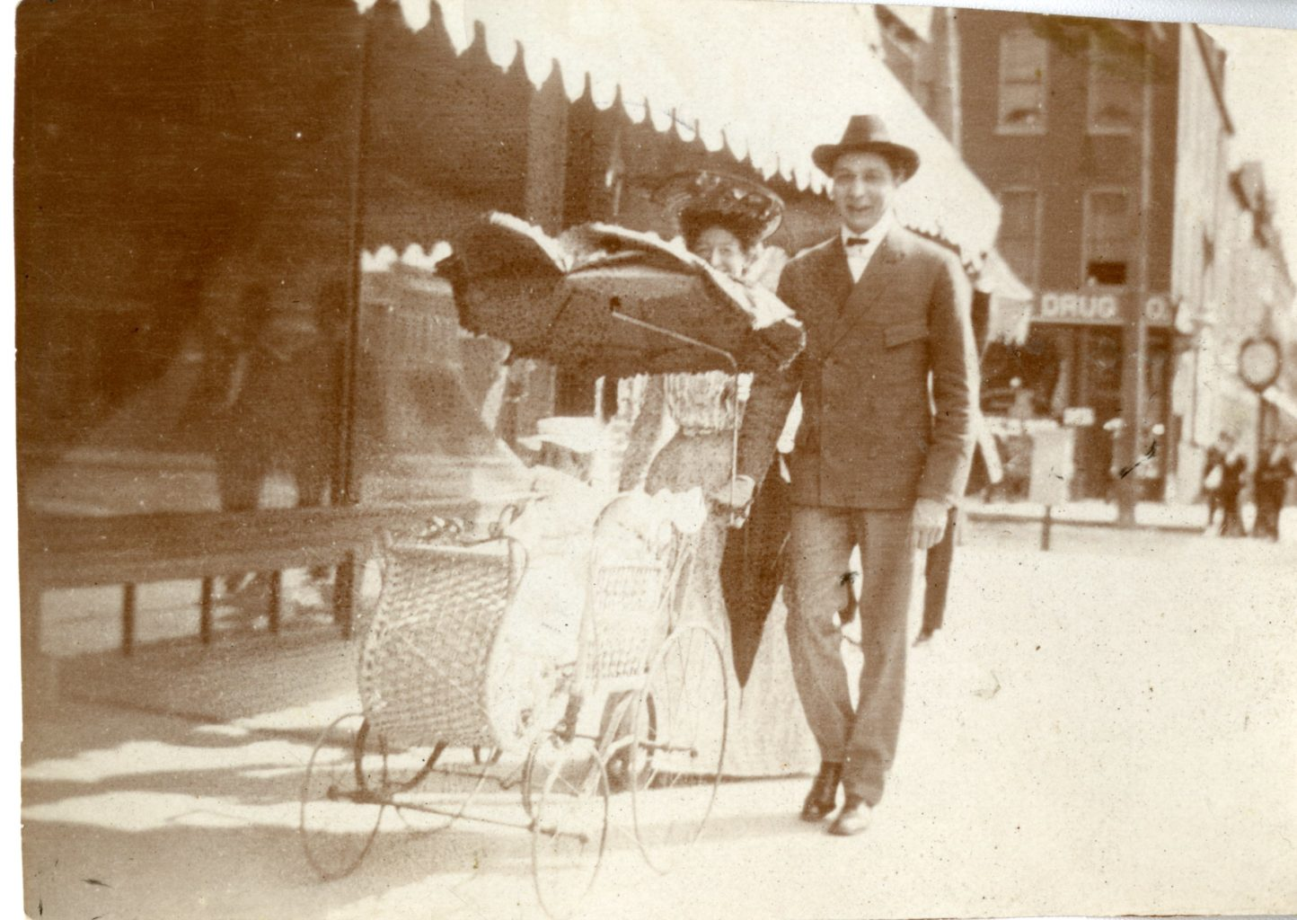 A husband and wife push their baby in a stroller down the sidewalk in a city.