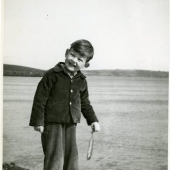 A small child, Miles Comwall, holds a fish.