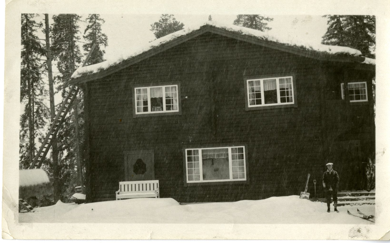 A man stands outside of a large house.