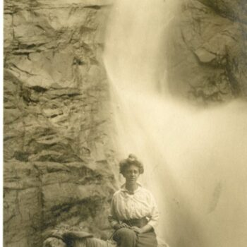 A woman, Nora Bernts, sits on a donkey in front of a waterfall.