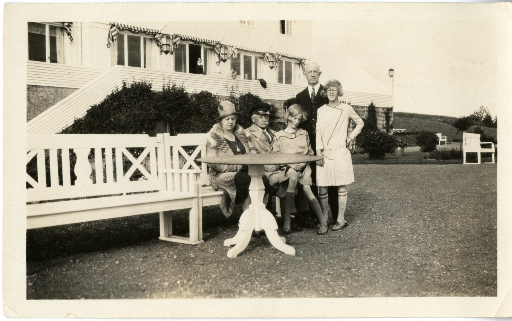 Five individuals outside a house. Three sit on a bench while two stand beside.