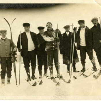 Seven men skiing.