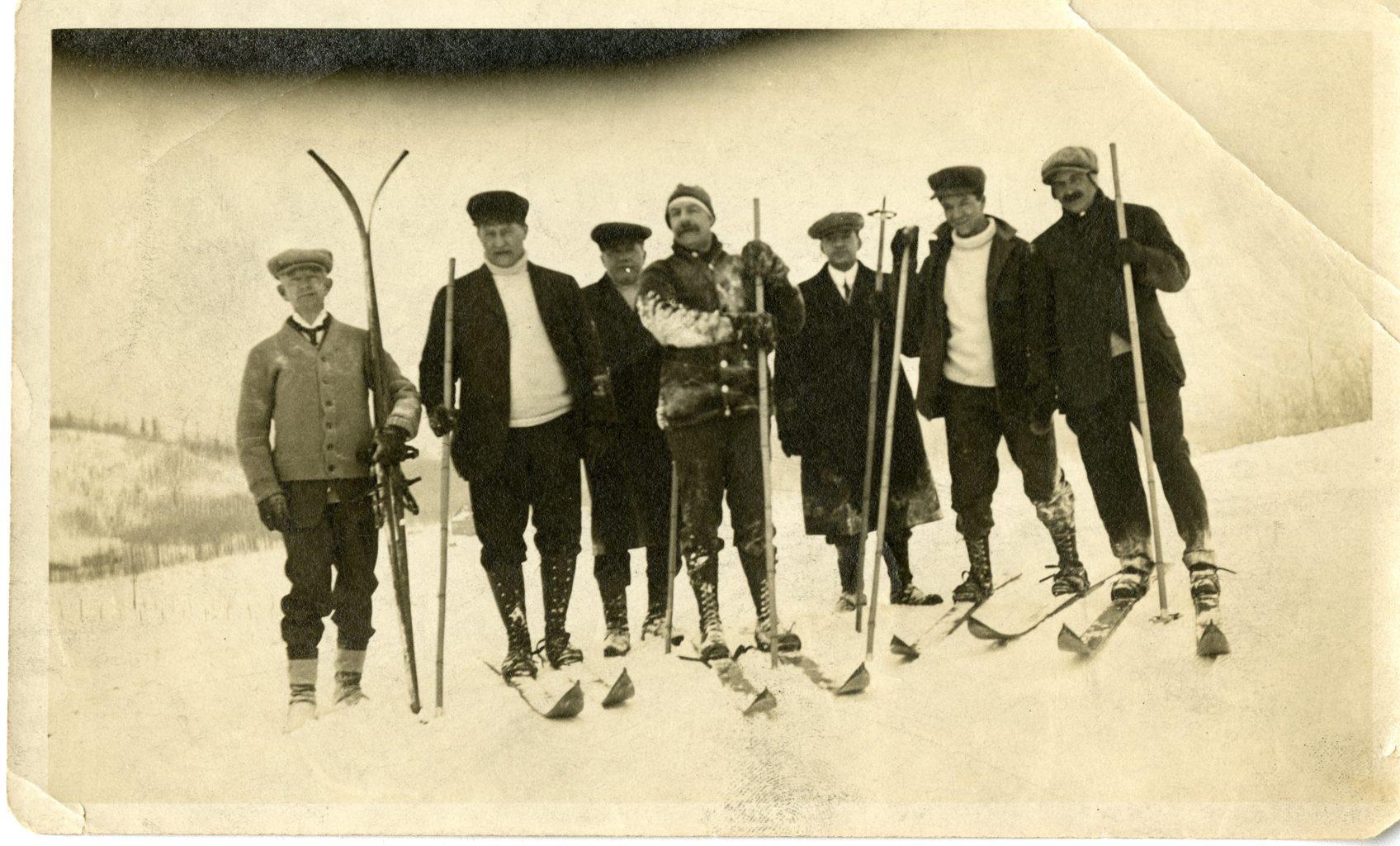 Seven men skiing.