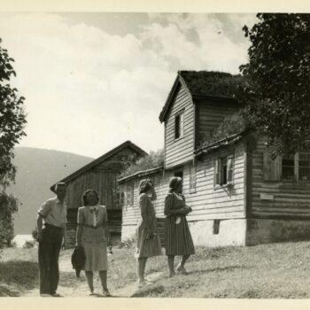 Four people, Ruar, Lotte, Randi, Akka, stand outside of a house.