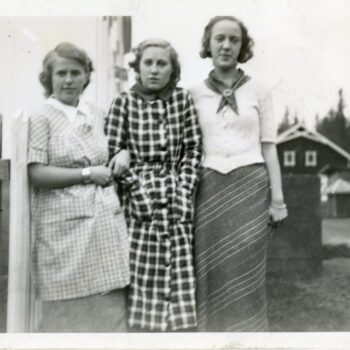 Three unidentified women stand along a fence. Norway