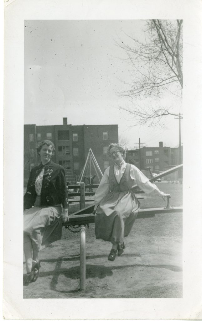 Two women on a teeter totter. One is wearing a bunad.