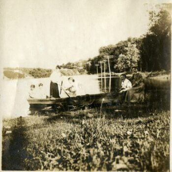 Six women sit in boat along marshy area.