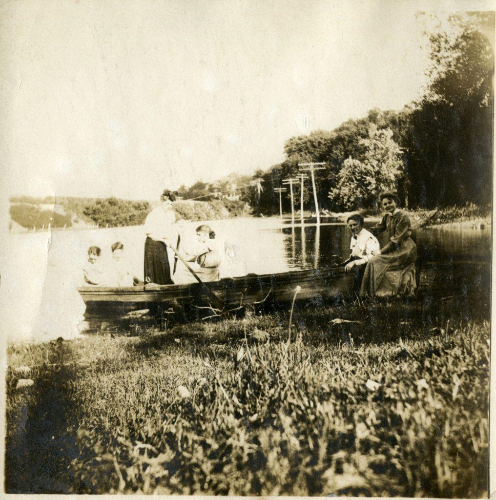 Six women sit in boat along marshy area.