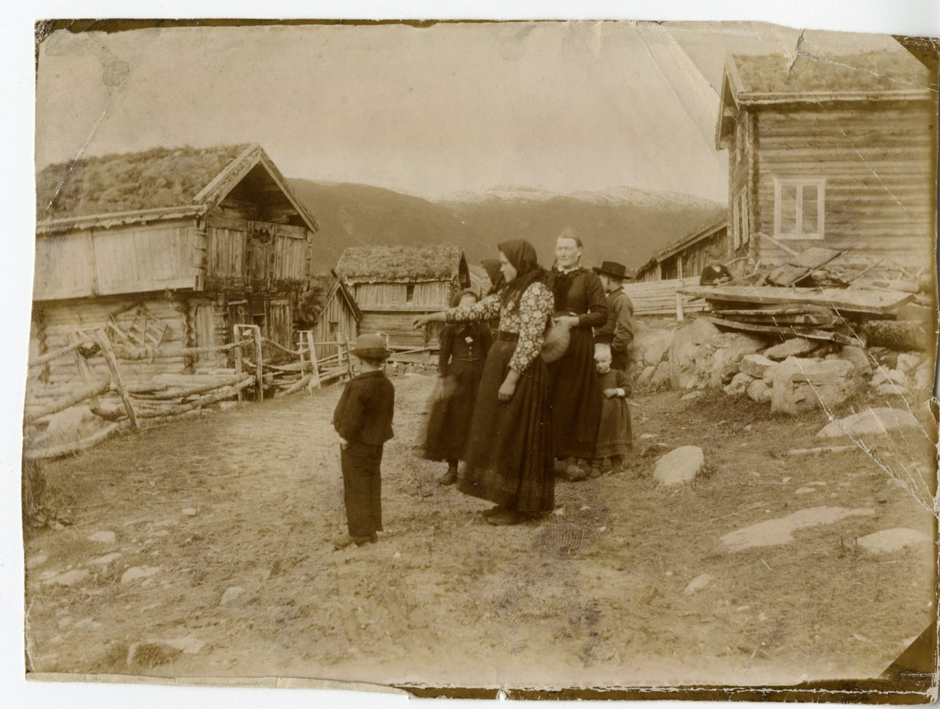Three adults and four children stand on the road, Midtgarden