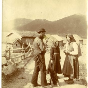 Man, woman, child, and dog stand on road and talk.