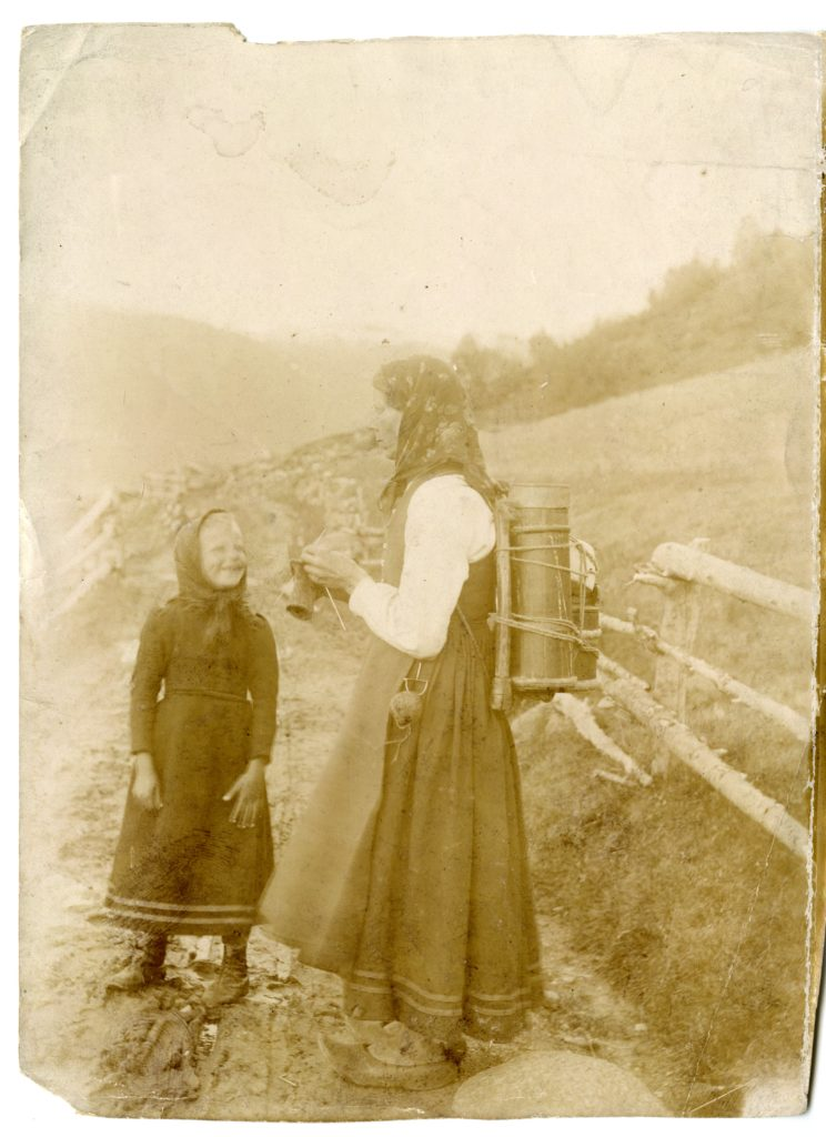Woman and child stand on road, woman knitting, child smiling.
