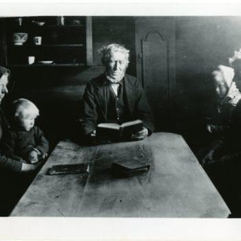 Man, woman, and three children sit around table.