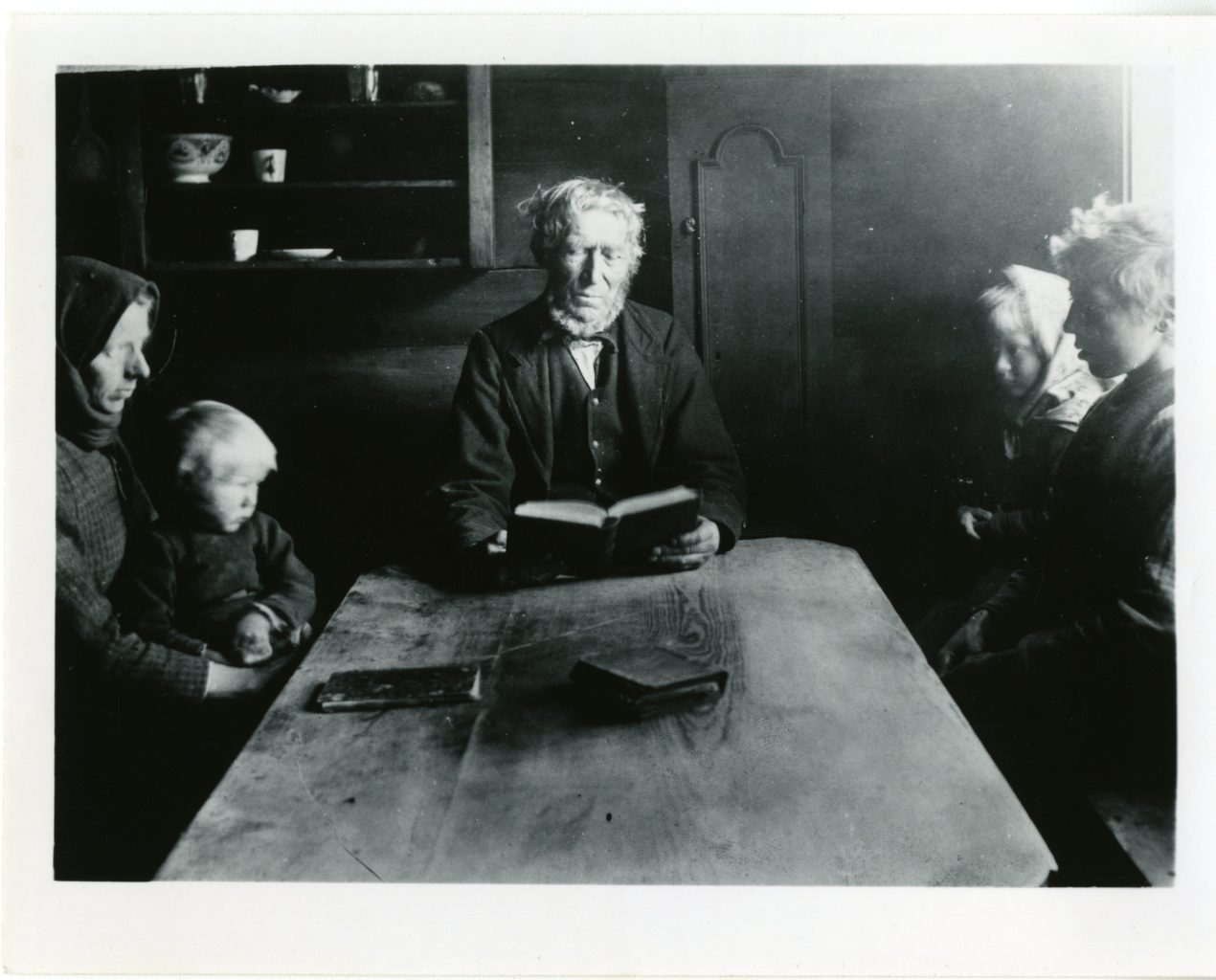 Man, woman, and three children sit around table.