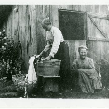 Mrs. Bruflodt and Anne Gausta outside of farm. Mrs. Bruflodt washes clothes, while Anne sits beside with dog.