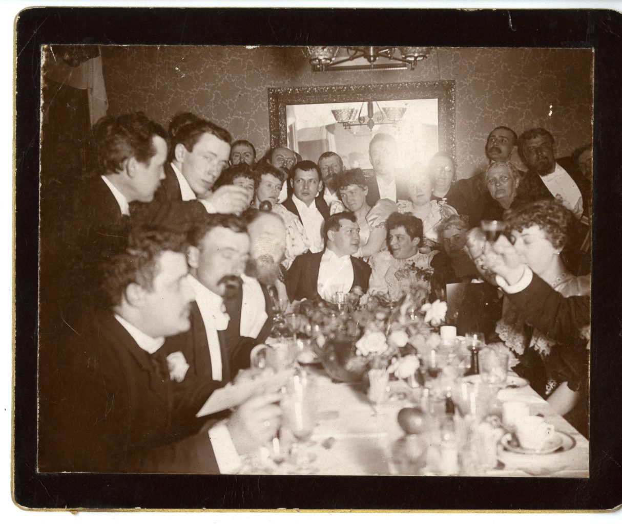 Large group of people in nice dress around a table.