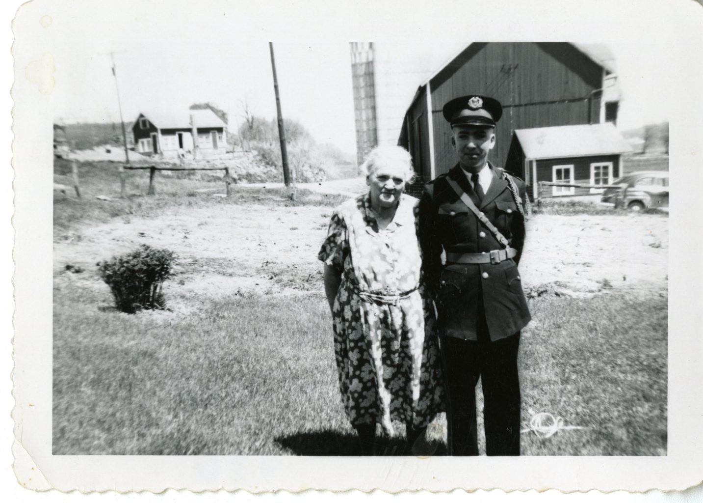 Mrs. Koeninger and George pose for photo outside on farm.