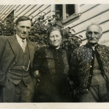Three individuals posing for a photo outside of a house.
