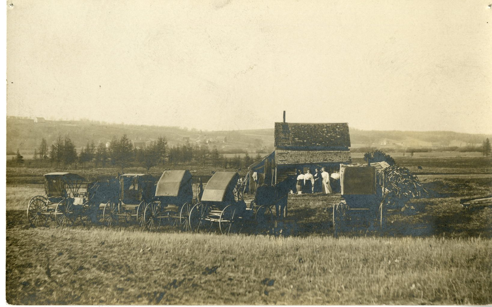 Group of women at farm with many horse and buggies.