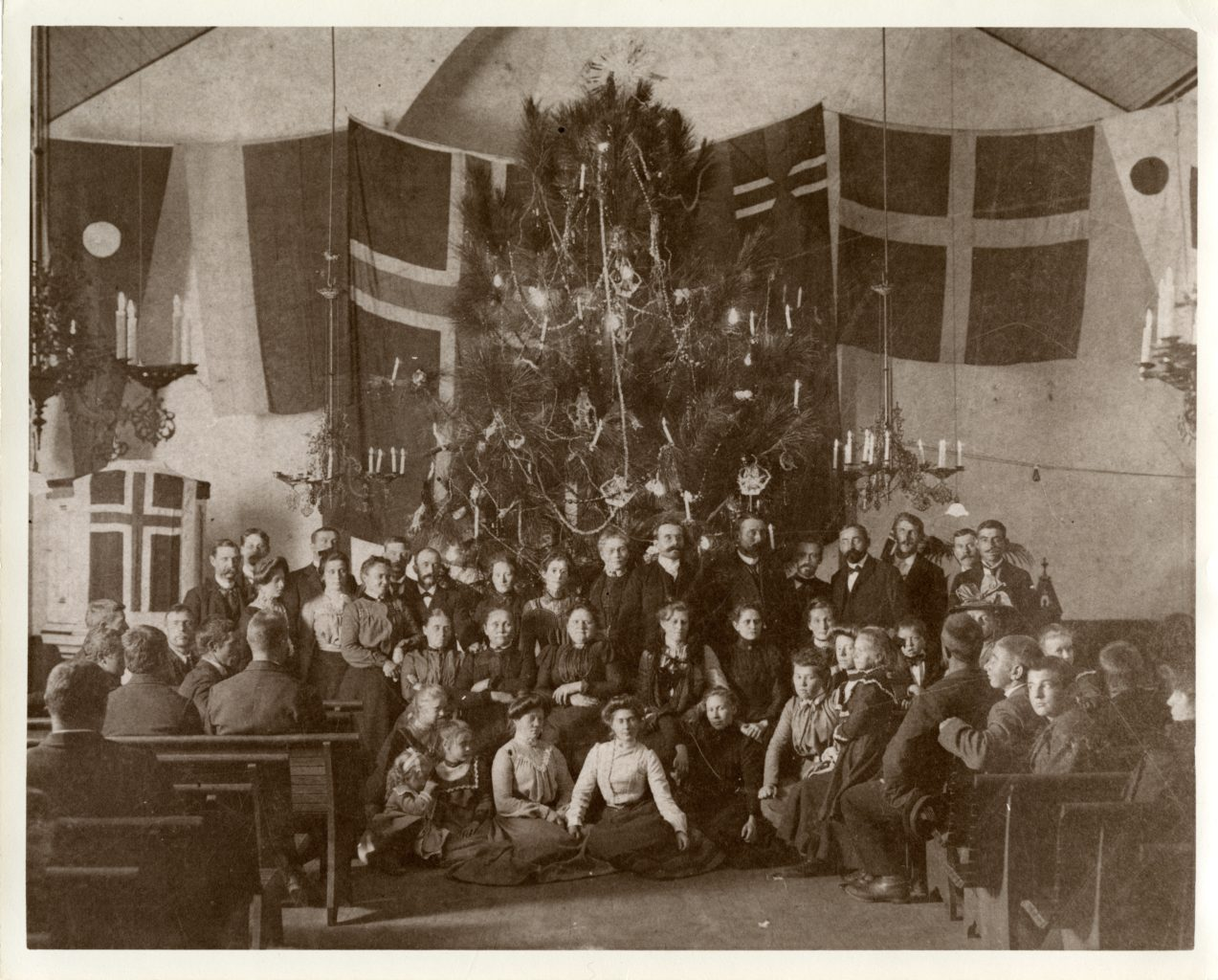 Large group photo of members of the church. Christmas tree decorated and Norwegian flag behind.