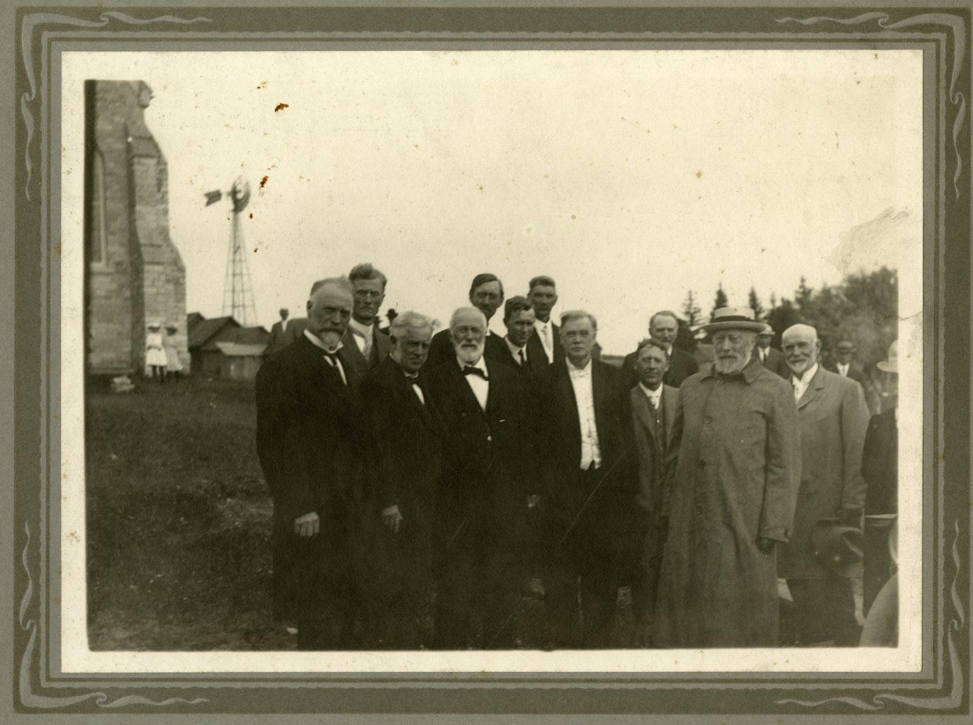 Group of men pose for photo with Bishop Brockman at Washington Prairie.